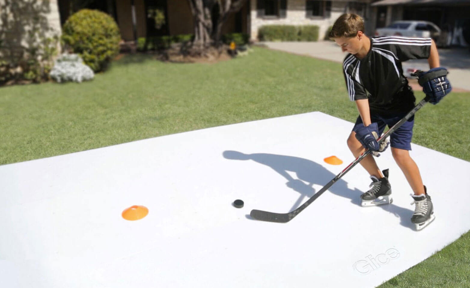 Boy training stick handling on synthetic ice sheet