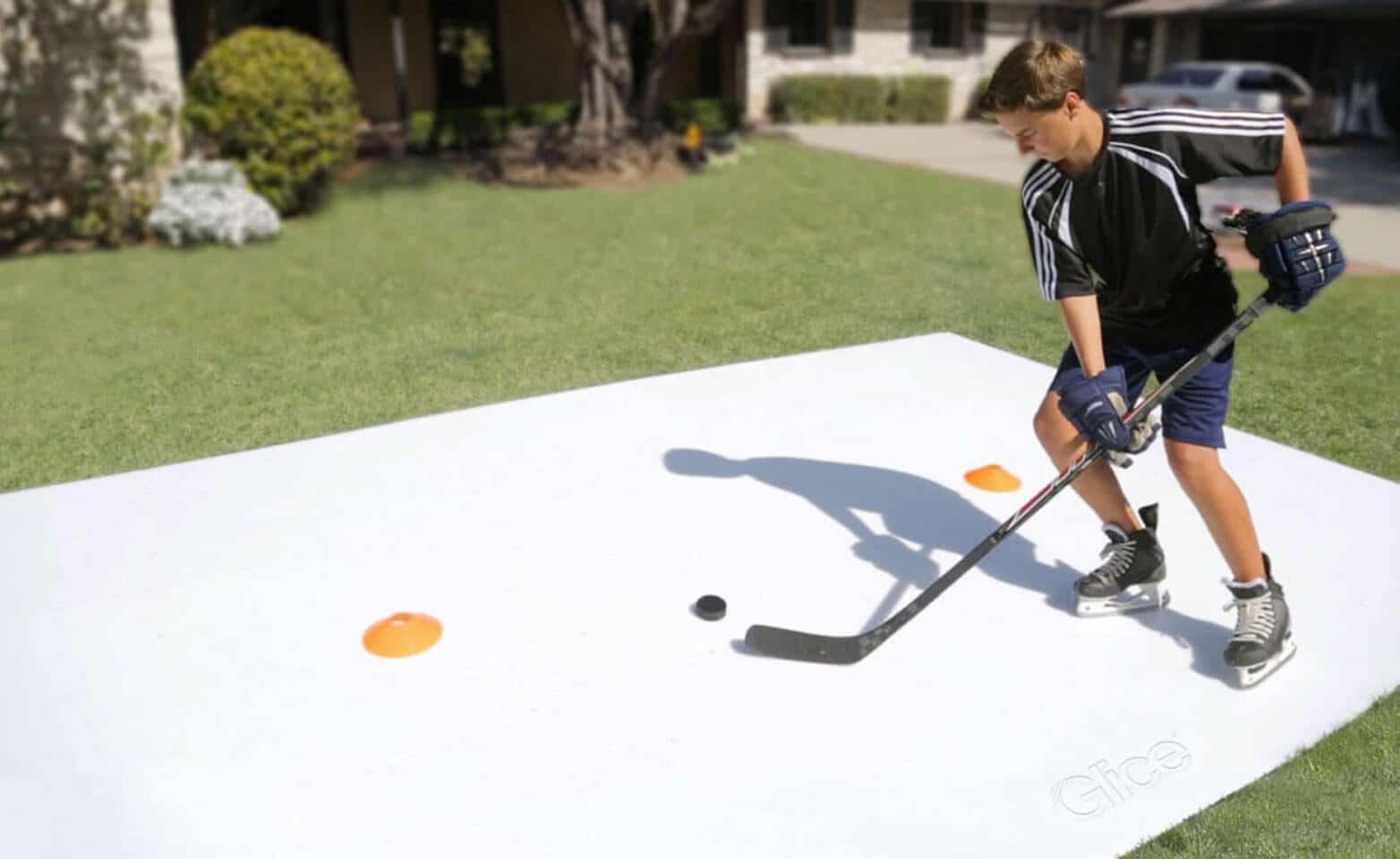 Boy training stick handling on synthetic ice sheet