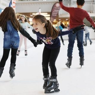 Children having fun on synthetic ice rink at Swiss mall