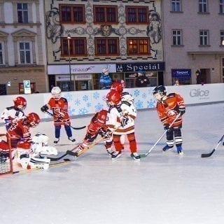 Children hockey match in city center on synthetic ice rink