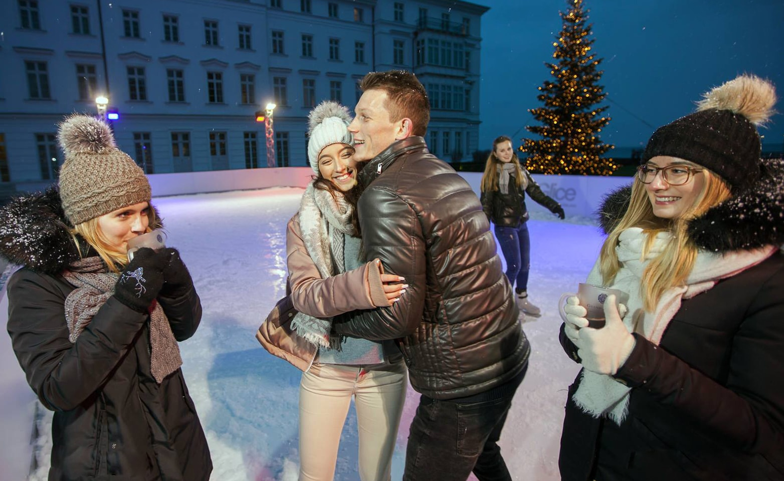 Couple enjoying Christmas season on synthetic ice rink at German Grand Hotel Heiligendamm