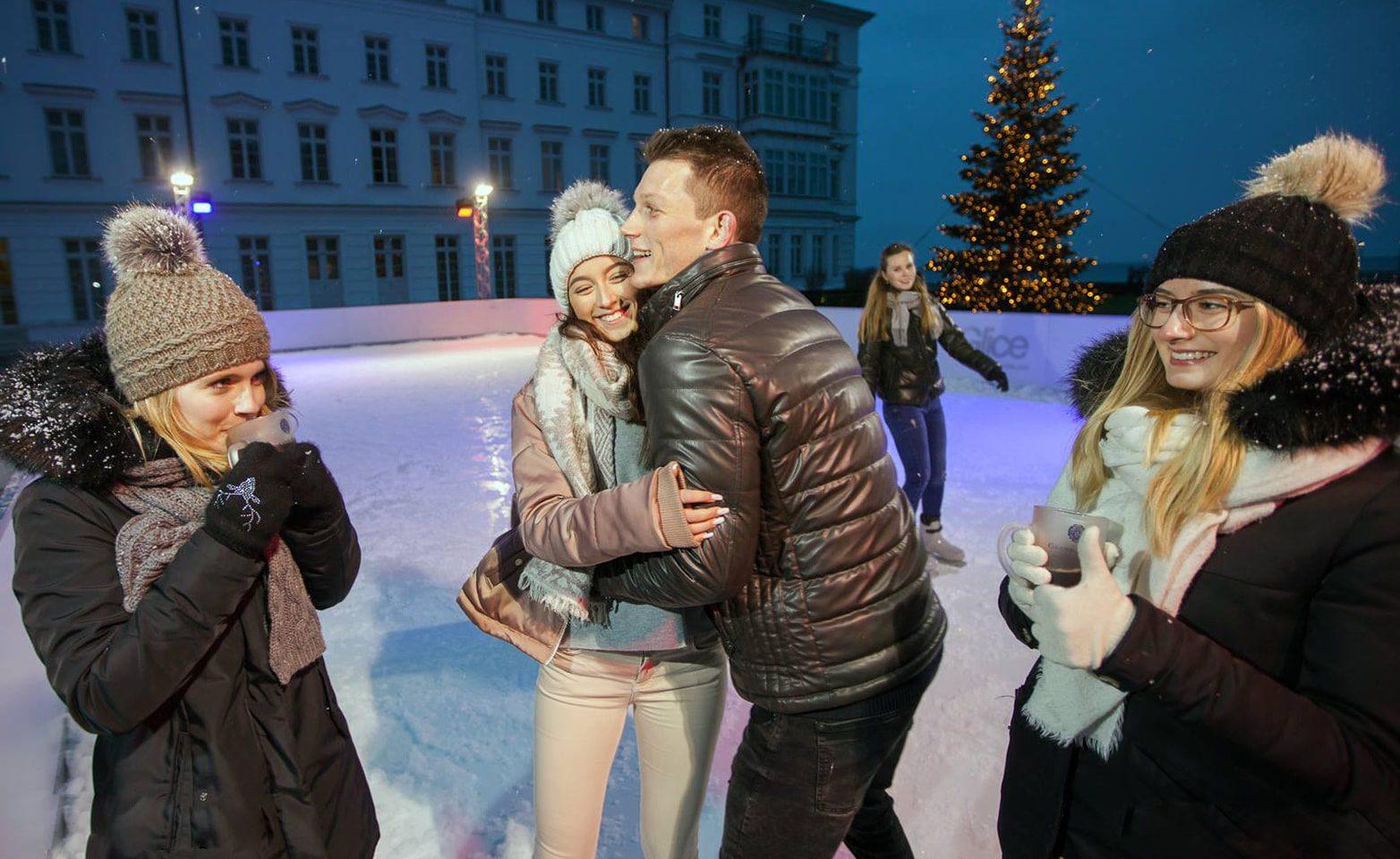Couple enjoying Christmas season on synthetic ice rink at German Grand Hotel Heiligendamm