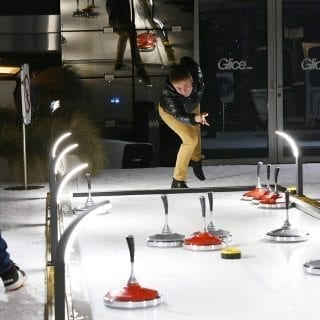 Eisstock curling game on synthetic curling lane