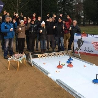 Employees enjoying Eisstock game on synthetic track at company event