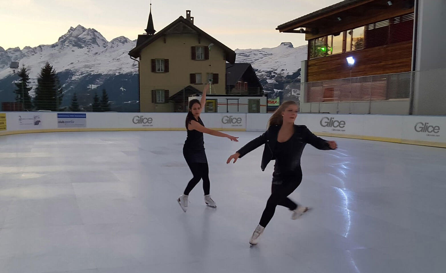 Figure skaters on artificial ice rink at famous Swiss ski resort