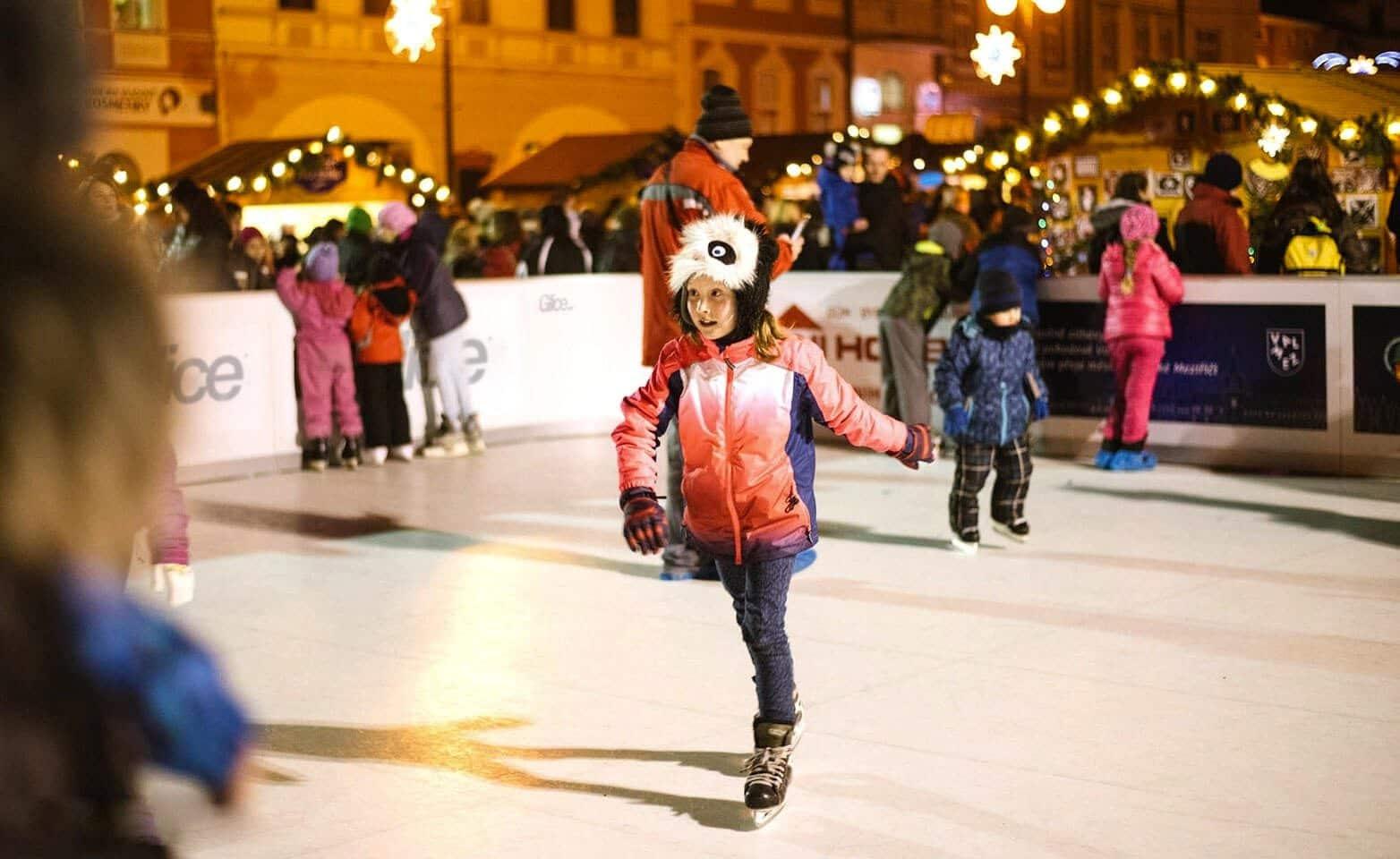 Girl skating on artificial Christmas rink