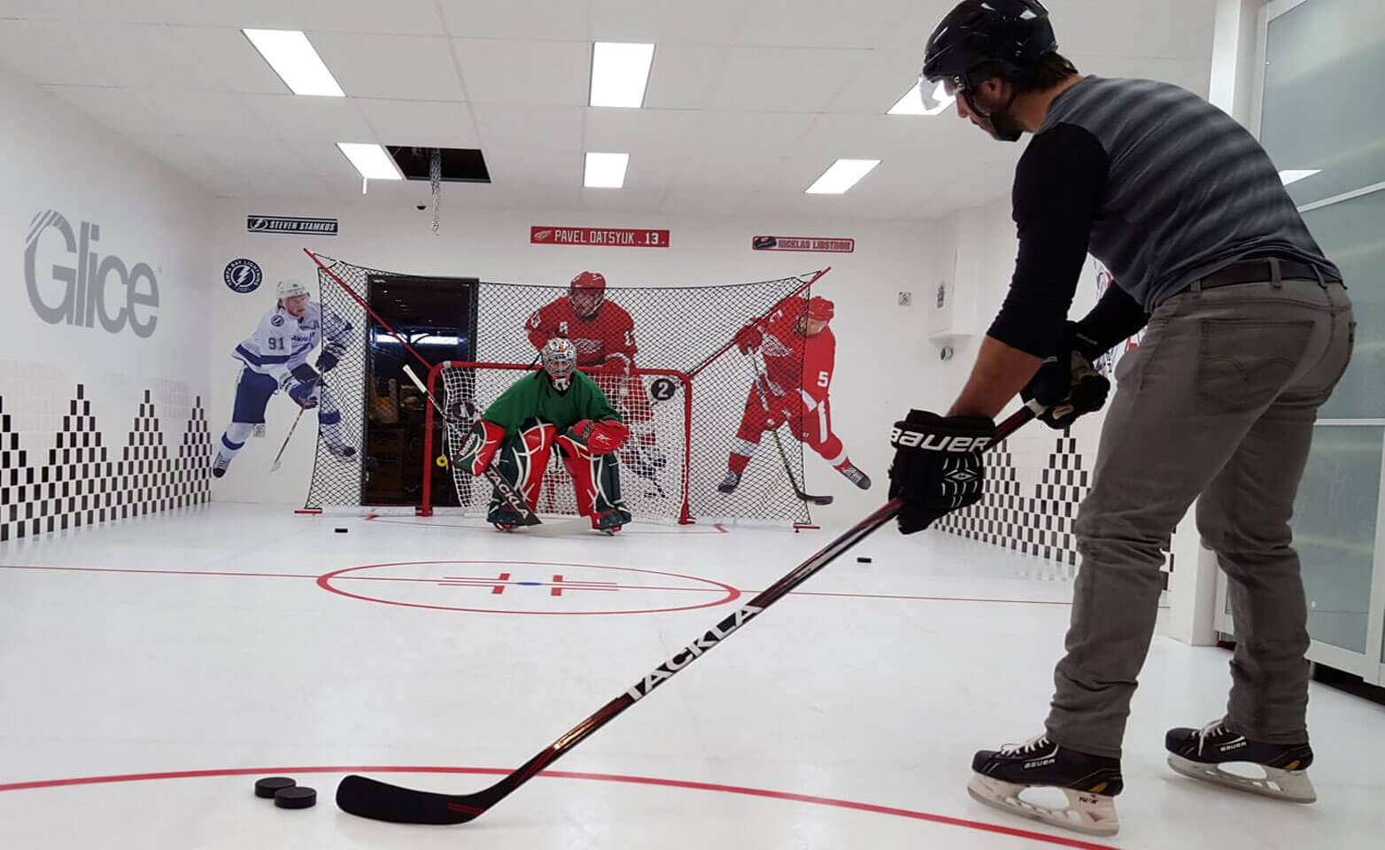 Hockey practice in synthetic ice rink with embedded hockey lines