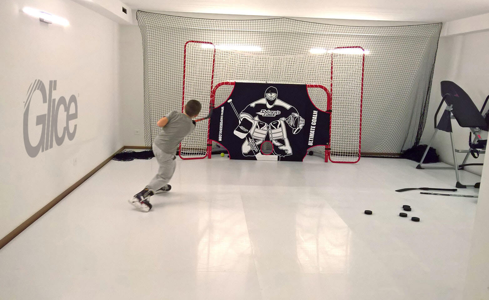Kid practicing shooting on plastic ice sheet