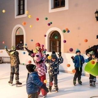 Kids having fun on plastic ice rink during Christmas season