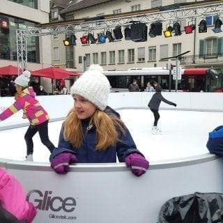Kids on a Christmas synthetic ice rink in Swiss town center