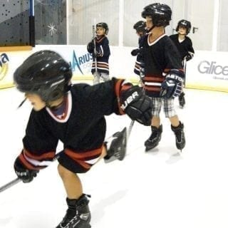 Kids playing hockey at synthetic ice rink mini arena