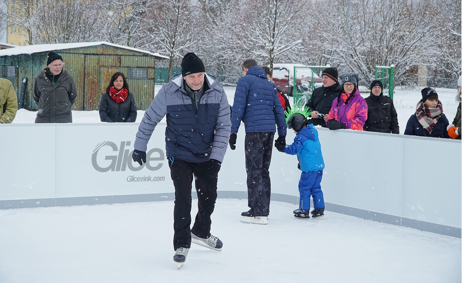 Man skating on synthetic ice rink while it's snowing