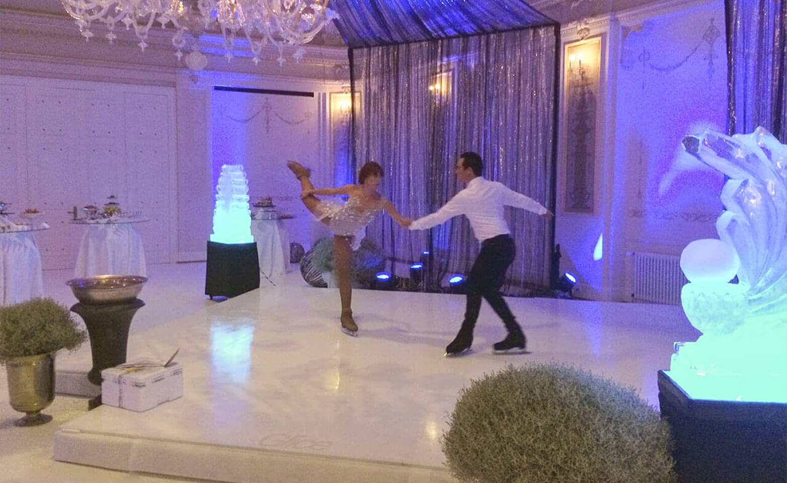 Professional figure skating couple performing on plastic ice pad at Swiss hotel