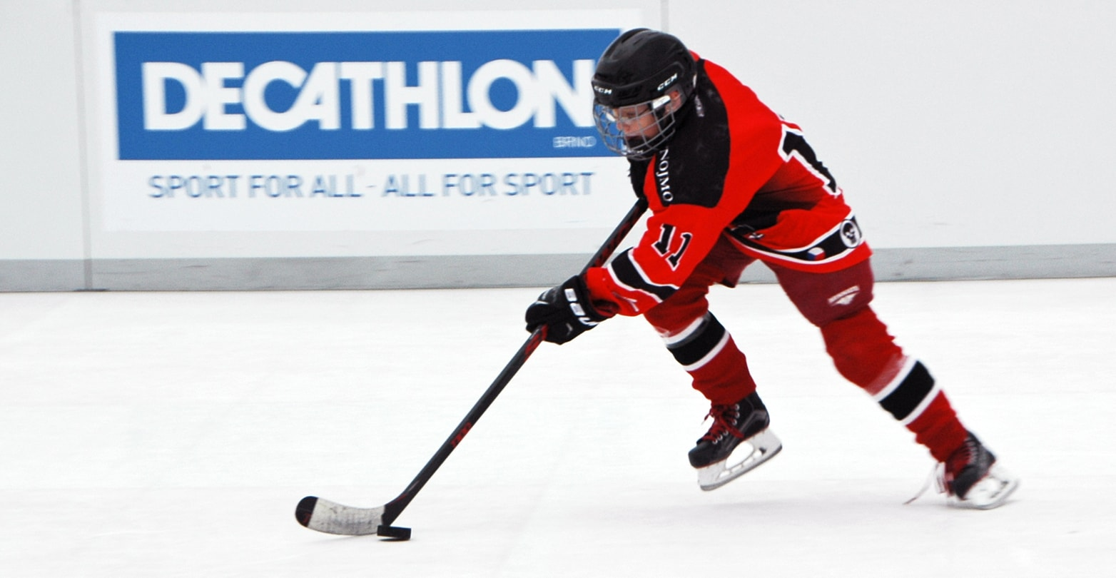 Ice hockey player gliding on artificial ice rink